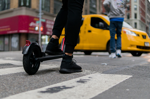 an electric scooter crosses the street near a yellow cab